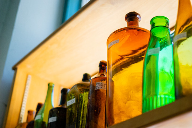 Colorful Antique Bottles and Containers Line a Shelf