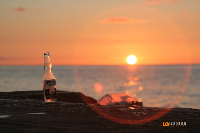 Aspettare il tramonto sugli scogli con una birra