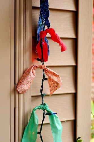 Vintage fabric scraps tied to Christmas lights | by toomanycommas