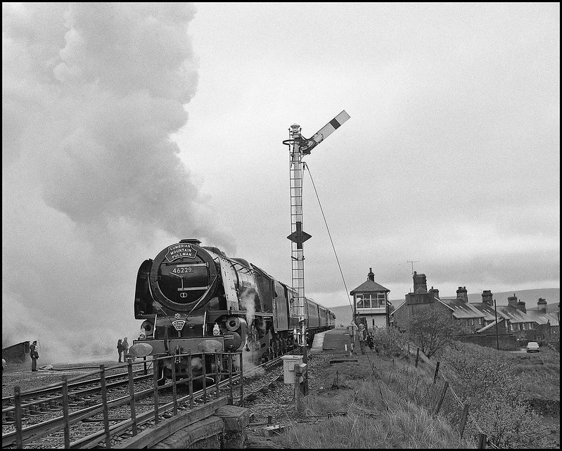 Decorated with the 'Blue Riband' in acknowledgement of record breaking performances on the S & C, 46229 departs from the Garsdale water stop under a threatening sky. Bill Allan is seen in customary pose on the right.