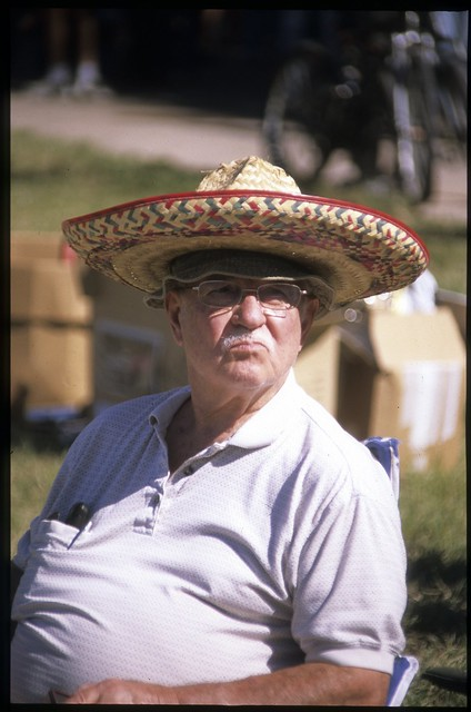 Old Man Sitting On A Folding Lawn Chair While Wearing A Sombrero Doing Duck Lips