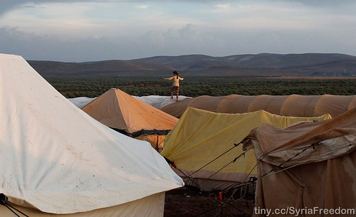 A child walks on top of a tent in a refugee camp in Atimeh on the Syrian-Turkish border on October 23, 2012. (Asmaa Waguih/Reuters   by FreedomHouse