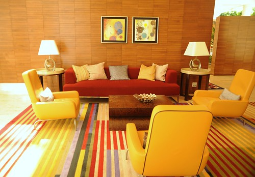 Lounge room, sofas, pillows, armchairs, end tables, lamps, art, wood walls, striped carpet, red and yellow, contemporary furniture, Renaisance Hotel, Schaumburg, Illinois, USA   by Wonderlane