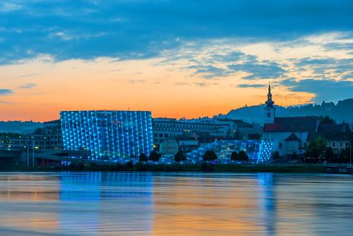 lumière reflet fleuve danube ville architecture moderne sunset couchédesoleil couleur bleu clocher nuage orange linz oberösterreich autriche