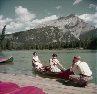 Two women canoeing on Bow River with Cascade Mountain in the background as a man on a dock photographs them, Banff, Alberta / Un homme accroupi sur un quai photographiant deux canoteuses sur la rivière Bow avec le mont Cascade à l'arrière-plan, Banff