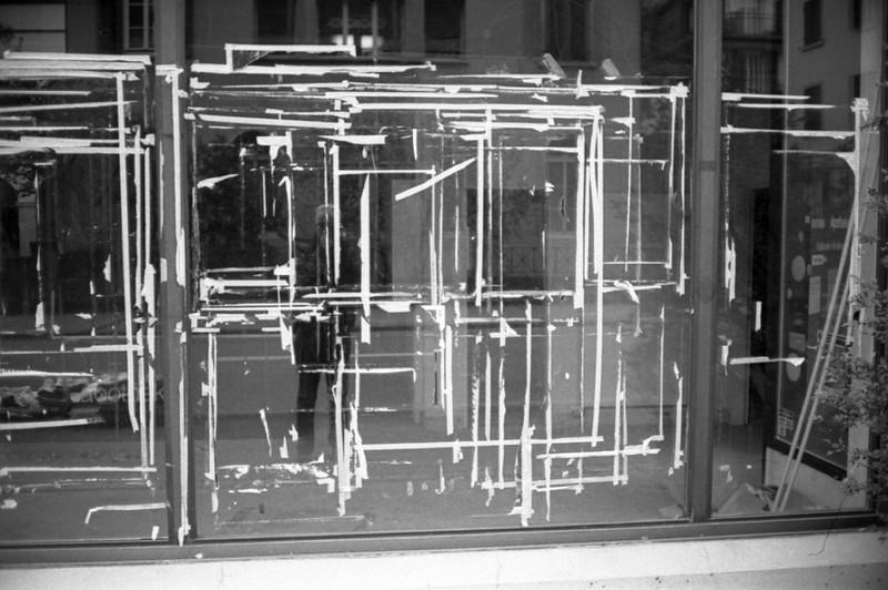 Scheibe verklebt mit Plakatresten und Spiegelung des Fotografen