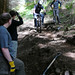 Sat, 08/04/2007 - 11:41 - On the 4th of August 2007 the Glentress Trailfairies decamped to Elibank forest in order to help prepare part of the course for the Selkirk Merida Marathon being held the following day.  With the fettling of this section largely complete a trailfairy gives it a test ride while Andy, Kenneth and Matthew look on, making sure that the stone step stays steady as the bike goes over it.
