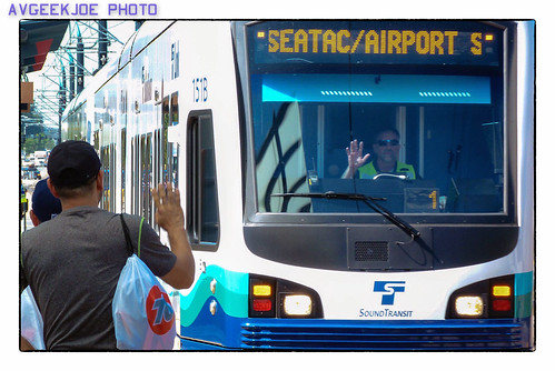 A Light Rail Driver and A Passenger Wave