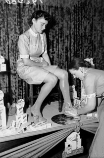 Young lady having Glaide liquid hosiery applied to her legs in a store, Brisbane, September 1941