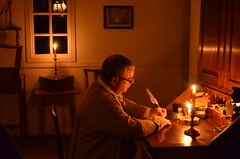 Merchant writing a letter by candlelight. Colonial Williamsburg