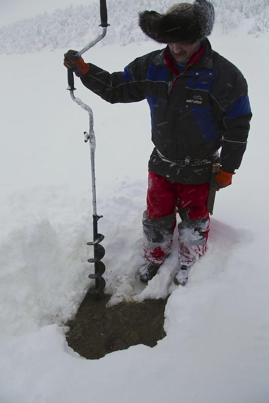 Oskar preparing a hole for ice fishing