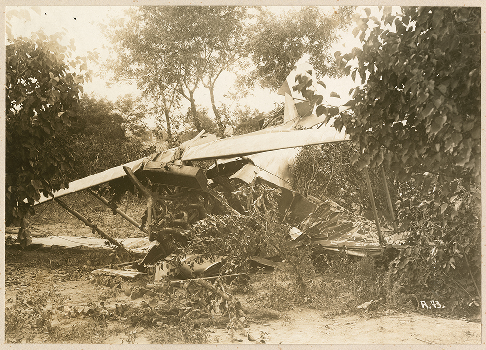 [Biplane wreckage in brush]