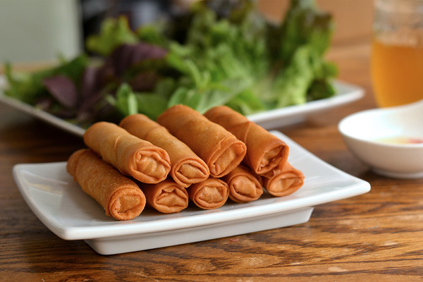 Egg rolls on a white plate with lettuce