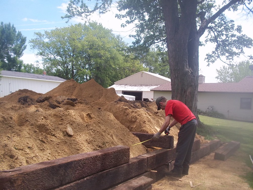 Railroad tie retaining wall | The yard needed a gravel pad s