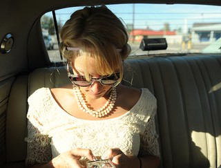 Jessie texting friends in her cream colored lace day frock, sun, sunglasses and pearls, wedding day, from the back seat of her fiancé Chris's classic car, Fairbanks, Alaska, USA | by Wonderlane