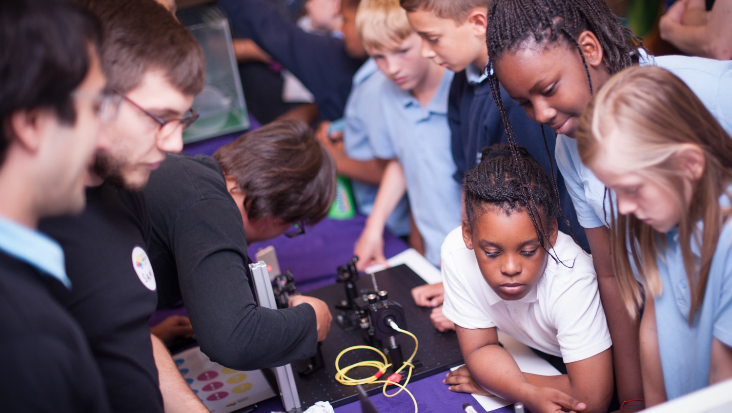 School children enjoying a science fair. They are hunched over watching intently an electronic experiment hosted by three adults.