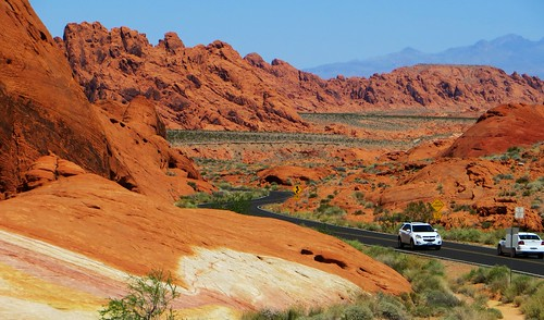 Winding road through large red rock hills, with a mountain in the background