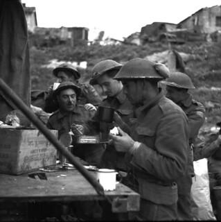 Personnel of the Loyal Edmonton Regiment having tea and sandwiches outside Battalion Headquarters... / Des membres du Loyal Edmonton Regiment prennent une pause thé et sandwiches à l'extérieur du quartier général du bataillon...