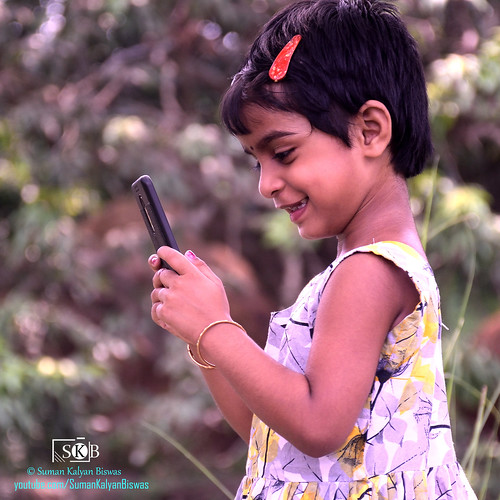 child kids mobilegaming portrait kid portraiture emotion garden candid park outdoor happy fun smile girl happiness mobile smartphone android androideffect happyface childhood kidding game play enjoyment entertainment india expression nadia westbengal