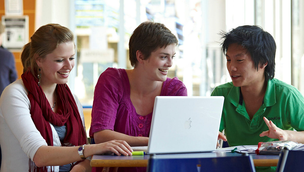 3 people looking at a laptop