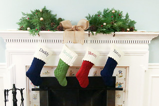 Christmas Mantel with pine centerpiece, holly and ribbon decorations and personalized family stockings in front of fireplace | by PersonalCreations.com