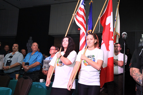 Female Youth Carrying Canadian and American Flags / Jeune fille tenant les drapeaux canadien et américain