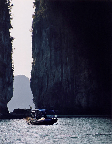 A Vietnamese Boat in the Shadow of Karst Cliffs in Halong Bay in Vietnam
