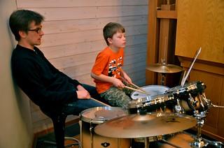 Två generationer Hjortlinger. En spelar trummor och en sover.