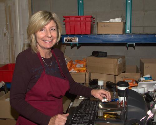 Female Worker with Apron Sitting at Computer / Travailleuse portant un tablier devant l'ordinateur