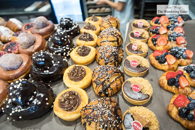 Large doughnuts, filled croissants and tarts in the display case (part of the many things available here)