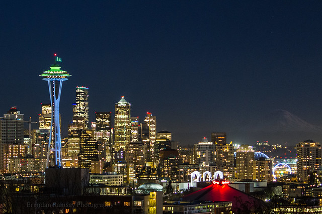 An hour after sunset and Mount Rainier National Park is still visible in the Blue Hour. And the Space Needle all decked out to represent the Seattle Seahawks and the 12th fan. — at Kerry Park.