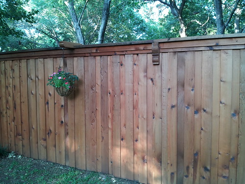 Board on board stained cedar fence with top cap, double trim and decorative accents/plant hangers.  North Richland Hills, Texas | by buzzcustomfence