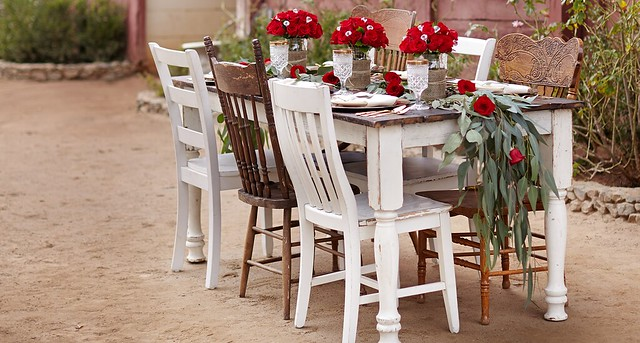 The Bachelor viewing party with a rustic theme with red roses wood chairs and a table next to a barn
