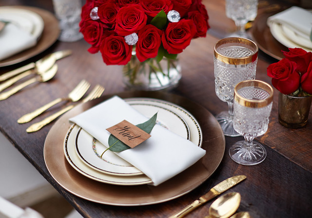 place setting for The Bachelor viewing party with a rustic theme red roses in a glass vase plates silverware napkin