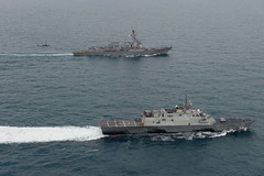 USS Fort Worth (LCS 3), USS Sampson (DDG 102), and an MH-60R Seahawk from Helicopter Maritime Strike Squadron (HSM) 35 operate together in the Java Sea, Jan. 14 while supporting the Indonesian-led search effort for AirAsia flight QZ8501.  (U.S. Navy/MC2 Antonio P. Turretto Ramos)