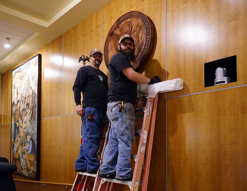 Jeremy Harris and Brad or Woodlab installing custom US District Court seal behind bench, McKinleyville 2015