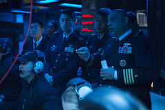 Capt. Kurush Morris, right, commanding officer of the guided-missile cruiser USS Shiloh (CG 67), explains operations to Japan Self-Defense Force officers during a Fleet Synthetic Training - Joint exercise. (U.S. Navy/MC3 Raymond D. Diaz III)