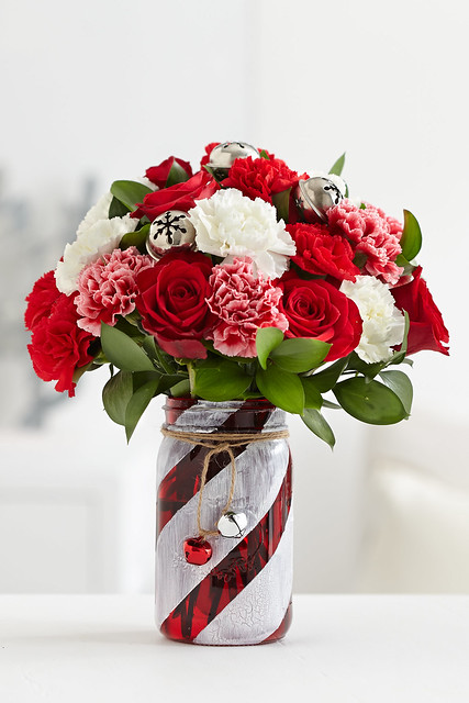 Finished red and white painted glass mason jar centerpiece vase with flower bouquet of red roses, pink and white carnations and jingle bells