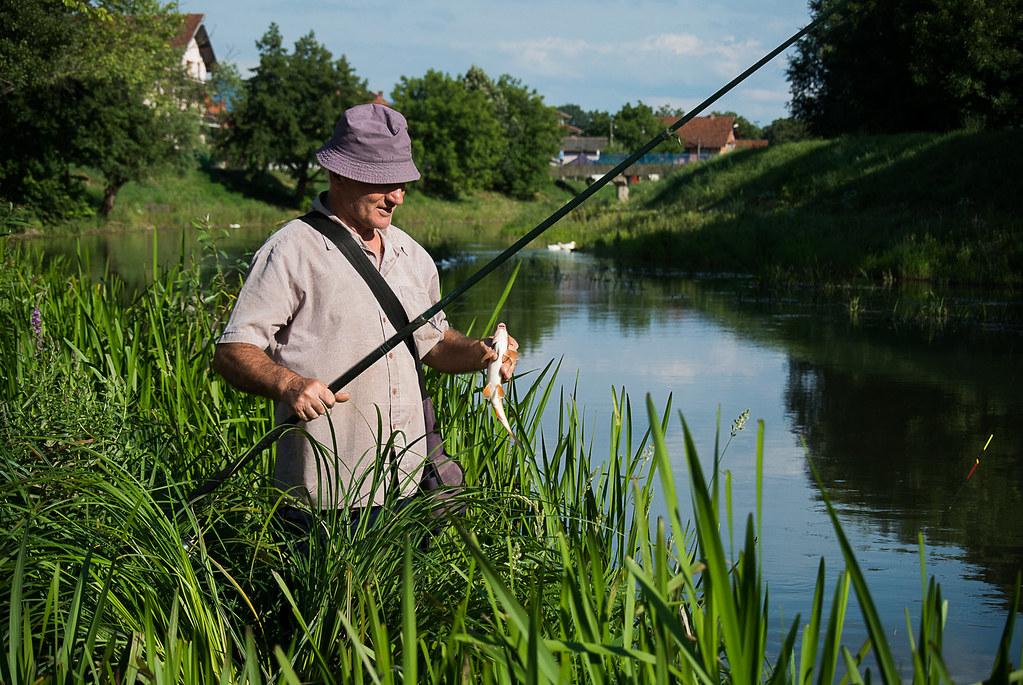 Fischer hält seinen Fang in der Hand