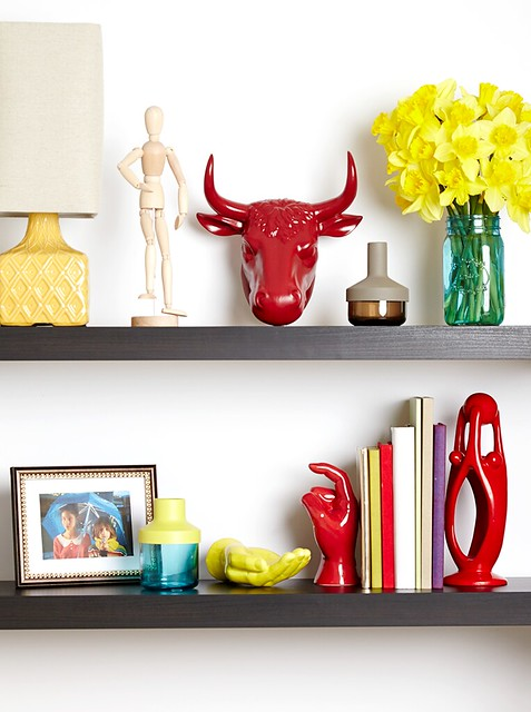 red bulls head posing aart figure daffodils in blue mason jar glass vase hand art picture in frame lamp and books on shelves