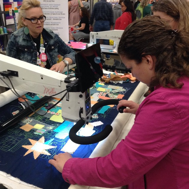My sister quilting on the longarm at the @overthetopquilting APQS booth