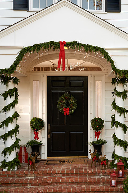 House front porch decorated for Christmas with pine garlands wreath red ribbon bows and decorative reindeer