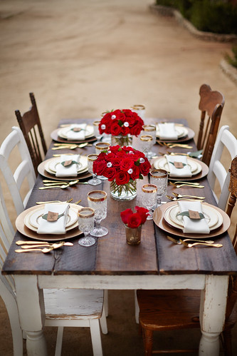 place setting for The Bachelor viewing party with a rustic theme red roses in a glass vase plates silverware napkin | by ProFlowers.com