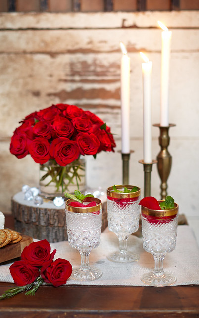 rustic table setting for The Bachelor viewing party with red roses white candles in gold candlesticks