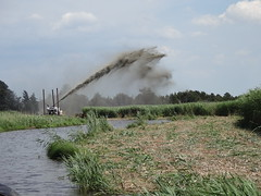 a channel of water and a machine blowing soil in the air