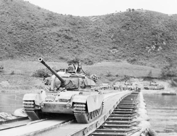 A Centurion tank passes over a pontoon bridge