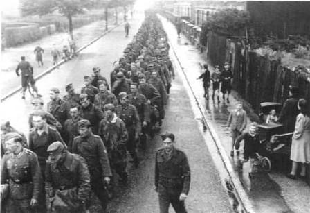 Columna de prisioneros alemanes marchan bajo vigilancia