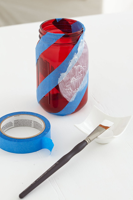 Red glass mason jar with blue tape around it being painted white with a paint brush