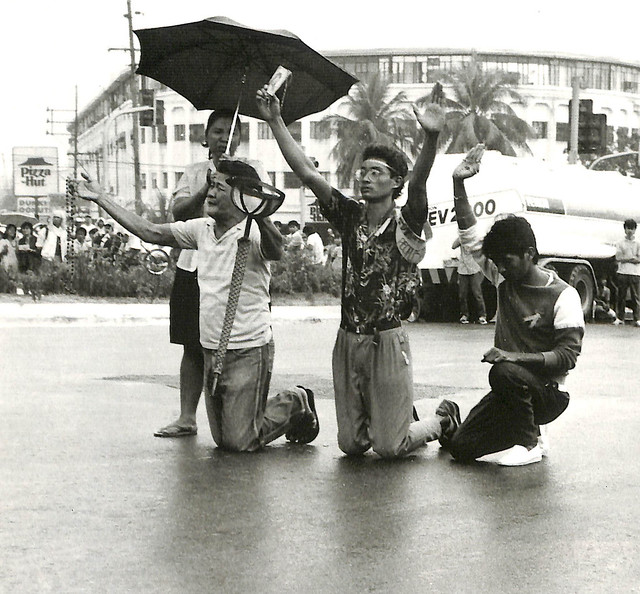 With umbrellas and rosary beads, citizens kneel on the streets in front of a column of tanks approaching in Quezon City