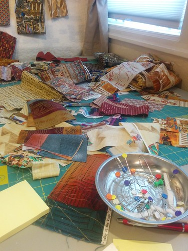 Several days in, the main table of potential mosaic pieces is organized chaos.  The finished quilt, and the story behind it, can be seen at domesticat.net/quilts/cairo-sunset